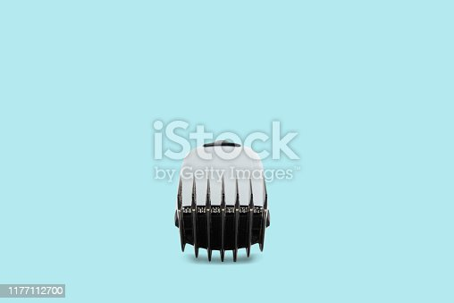 626808632istockphoto Hair clipper on a pastel blue background. The concept of cutting, improving the appearance. 1177112700