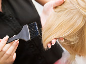 Hair coloring in a beauty salon in blonde. Hairdressing services.
