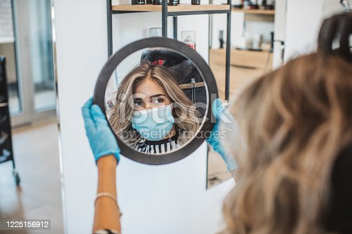 Young woman have hair cutting at hair stylist during pandemic isolation, she wears protective equipment