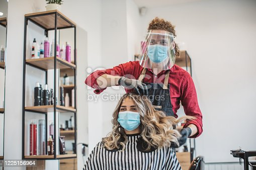 Young woman have hair cutting at hair stylist during pandemic isolation, they both wear protective equipment