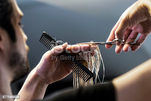 Hairdressers cutting hand with scissors and comb