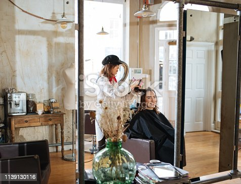 istock Hair dresser doing blow and dry 1139130116