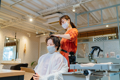 A female hair dresser s drying costumer's hair. the owner and the customer are wearing protective face masks for illness prevention.