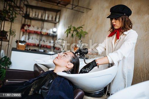 istock Hair dresser rinsing hair 1139129955