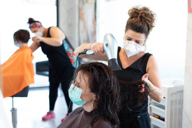 commode de cheveux travaillant avec un masque facial pendant la quarantaine de coronavirus - salon de coiffure photos et images de collection