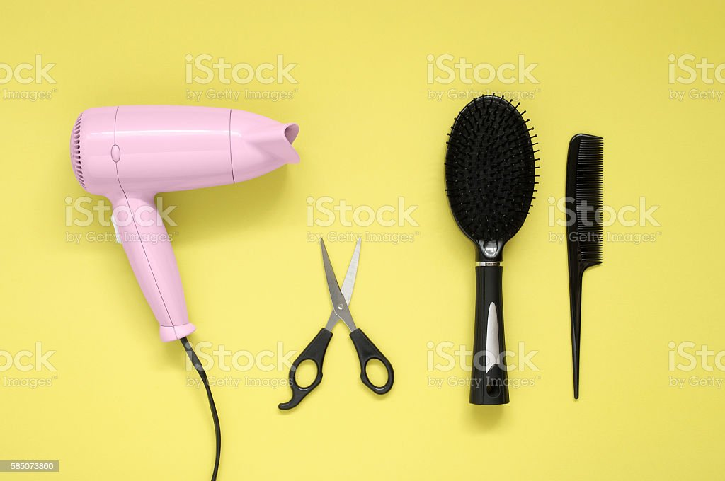 Hair dryer, brush, comb and scissors on yellow paper background stock photo