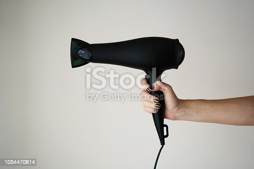 istock Hair dryer in woman's hand 1054470814