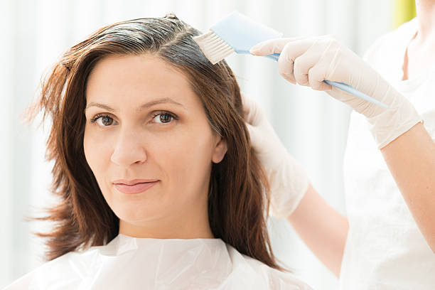 Hair Dye Portrait shot of a woman with brown hair in salon / Hair Dye medium length hair stock pictures, royalty-free photos & images