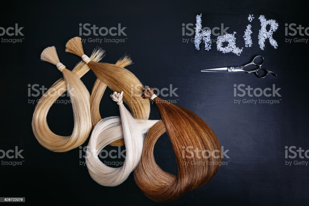 hair extensions of four colors on a dark background with scissors. copyspace. top view stock photo