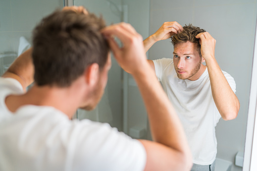 Hair loss man looking in bathroom mirror putting wax touching his hair styling or checking for hair loss problem. Male problem of losing hairs.