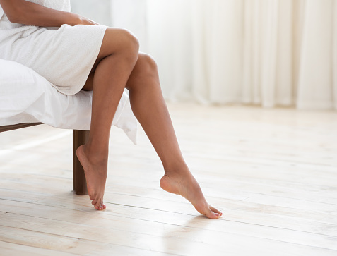 Hair removal, body care and female beauty. Beautiful slender legs of young african american lady in white towel after shower shaving, sits on bed in interior of bedroom in morning, cropped, copy space