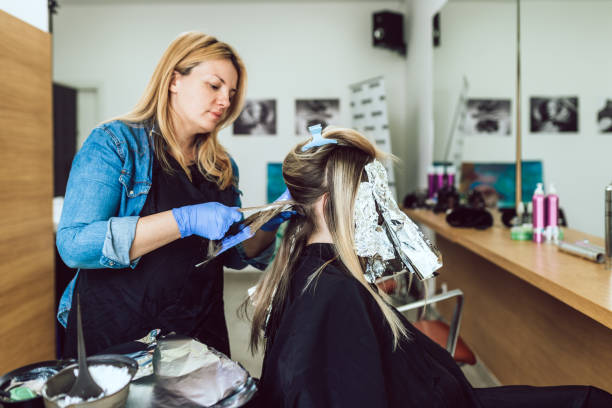 Hair salon Female hairdresser is dying woman's hair, making hair highlights to his client with a foil. highlights hair stock pictures, royalty-free photos & images