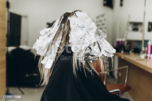 Female hairdresser is dying woman's hair, making hair highlights to his client with a foil.