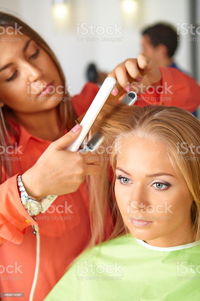 Hair salon. Woman haircut. Use of straightener. royalty-free stock photo