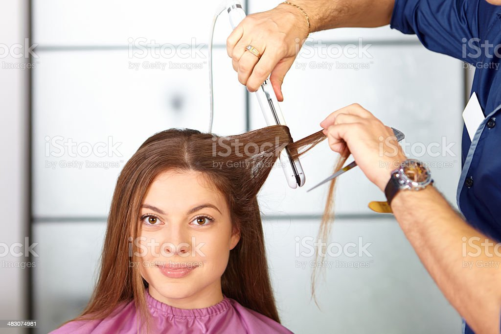 Hair salon. Woman haircut. Use of straightener. royalty-free stock photo
