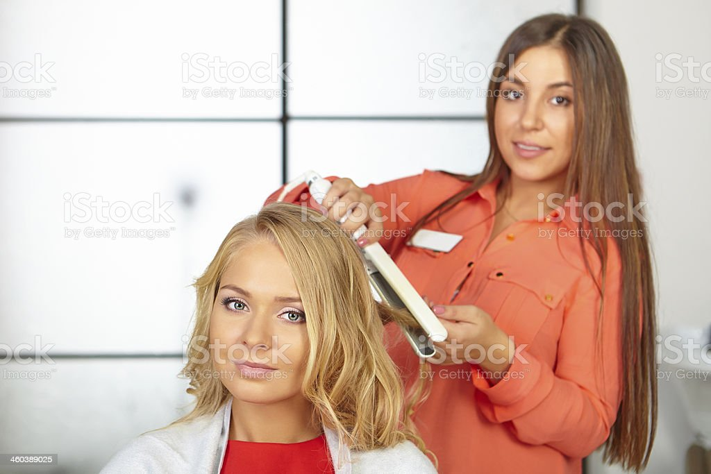Hair salon. Womens haircut. Use of straightener. royalty-free stock photo