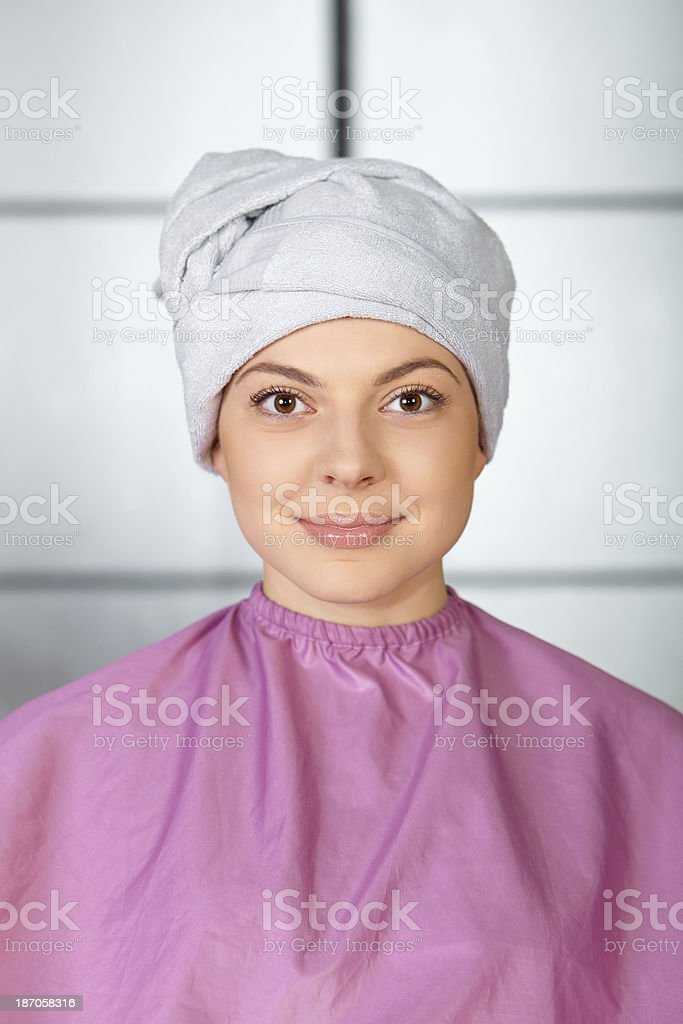 Hair salon. Young woman in hairdressing gown and towel. royalty-free stock photo