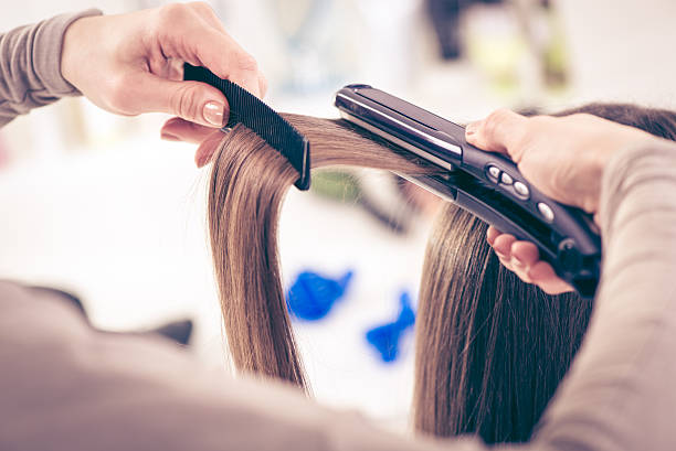 Hair Straighteners Close-up of a hairdresser straightening long brown hair with hair irons. straight hair stock pictures, royalty-free photos & images