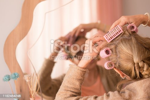 886414246istockphoto Hair Styling brunette brushing her hair before a mirror 1152454248