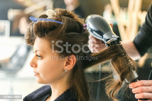 Attractive young woman at a hair salon with male hairdresser styling her hair. About 25 years old, Caucasian female.
