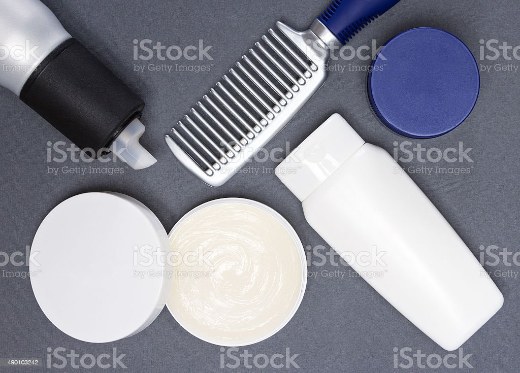 Hair styling products with comb on gray background stock photo