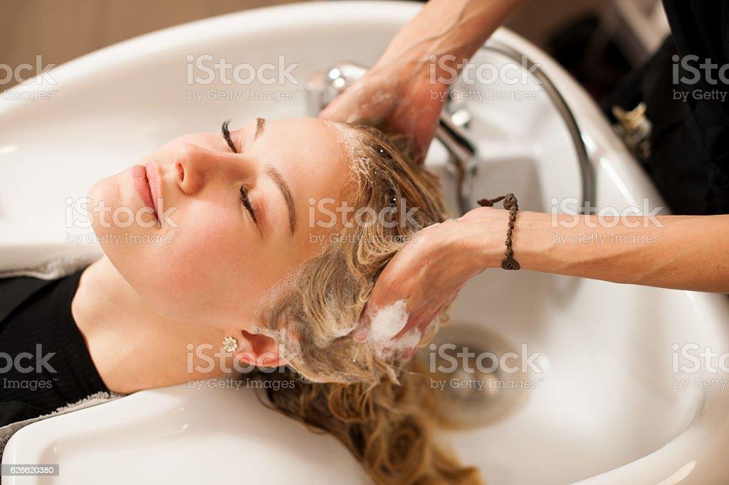 Hair stylist at work - hairdresser washing hair stock photo