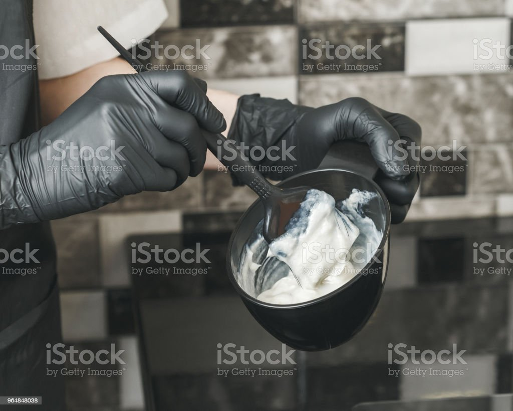 Hair stylist hands preparing a dye in a container royalty-free stock photo