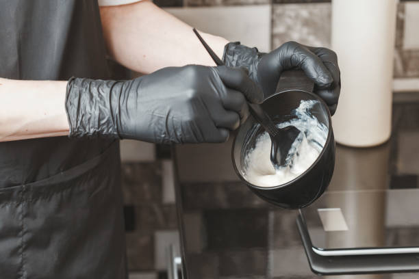 hair stylist hands preparing a dye in a container - capelli ossigenati foto e immagini stock