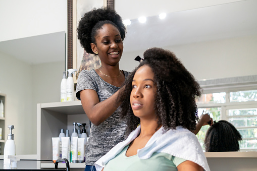 Photo of two brazilian woman. A client and a hair stylist.