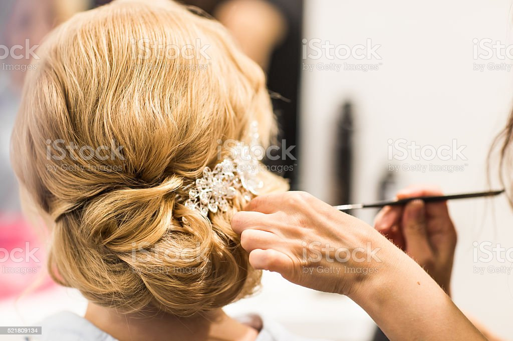 Hair stylist makes the bride before a wedding stock photo