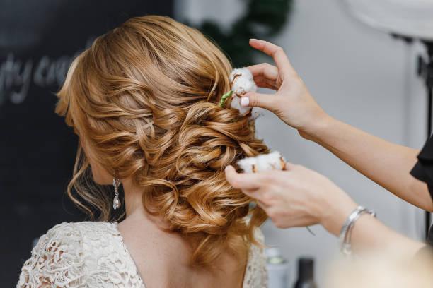 stylista włosów lub kwiaciarnia sprawia, że panna młoda fryzura ślubna ze świeżymi kwiatami bawełny - panna młoda zdjęcia i obrazy z banku zdjęć
