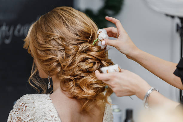 Hair stylist or florist makes the bride a wedding hairstyle with fresh cotton flowers stock photo