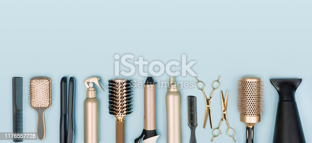 istock Hair stylist tools arranged in a line on blue background 1176557728