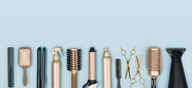 Hair stylist tools arranged in a line on blue background stock photo