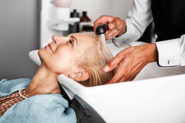 Haar-Stylist waschen reife Frau Haar – Foto