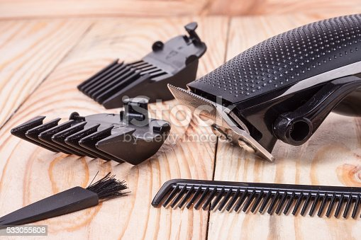 626488516istockphoto hair trimmer with attachment  and a comb on wooden background 533055608
