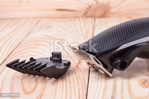 626488516istockphoto hair trimmer  with attachment on a light wooden background closeup 532176212