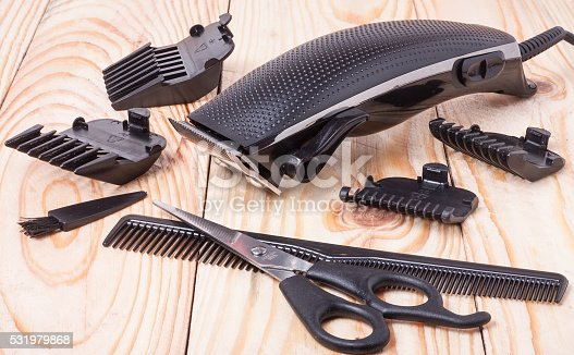 626488516istockphoto hair trimmer with comb and scissors on the wooden background 531979868