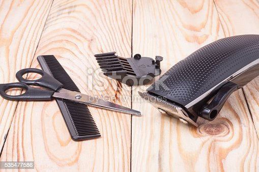 626488516istockphoto hair trimmer with comb and scissors on the wooden background 535477586