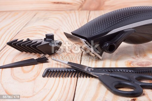 626488516istockphoto hair trimmer with comb and scissors on the wooden background 537907478