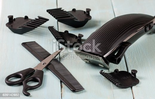 626488516istockphoto hair trimmer with comb and scissors on the wooden background 639142652