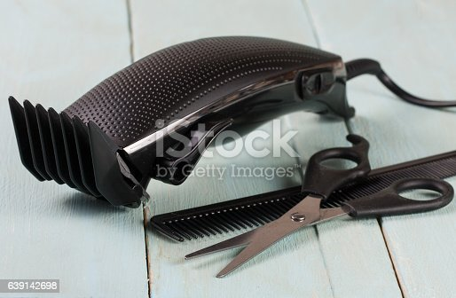 626488516istockphoto hair trimmer with comb and scissors on the wooden background 639142698