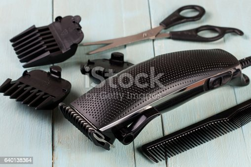 626488516istockphoto hair trimmer with comb and scissors on the wooden background 640138364