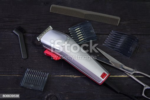 istock Hair trimmer with comb and scissors on the wooden background 806609538