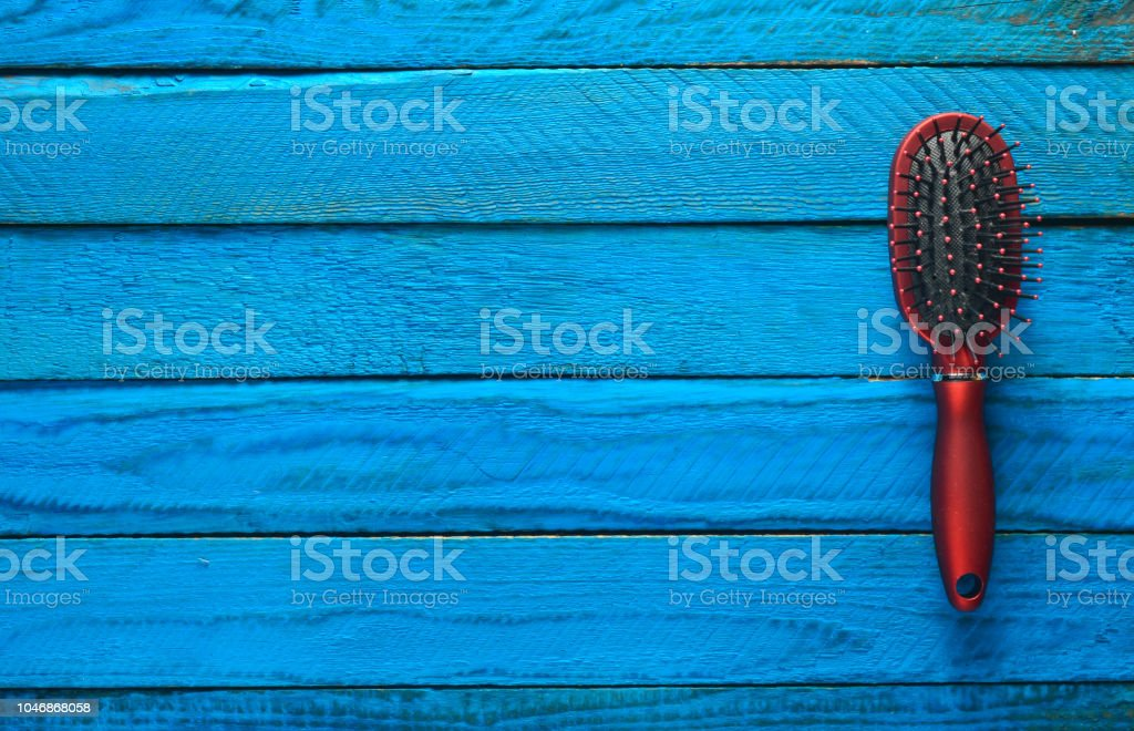 Hairbrush on blue wooden background стоковое фото