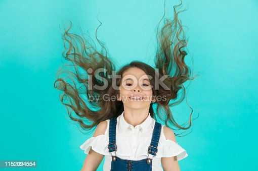 Haircare, hairstyle, hairdresser, barber. Girl smile with flying hair on blue background. Child smiling with long healthy hair. Beauty salon concept, punchy pastel