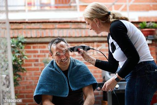 Woman cutting man's hair with electric razor at home during coronavirus quarantine.