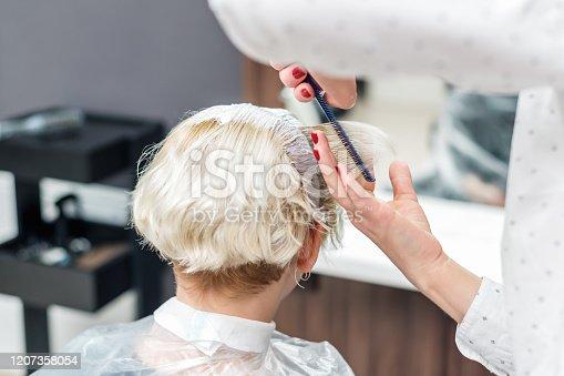 istock Hairdresser applies white dye. 1207358054