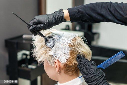 istock Hairdresser applies white dye. 1209039498