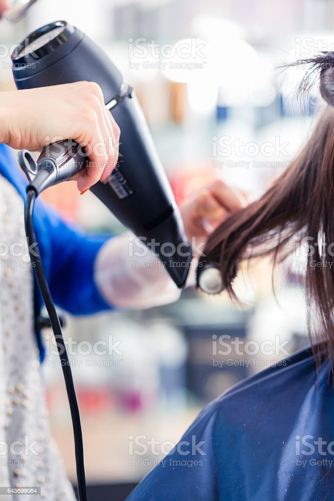 Hairdresser blow dry woman hair in shop stock photo